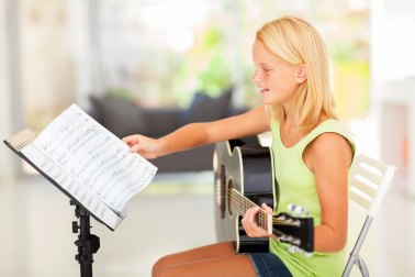 Girl Playing Guitar with Sheet Music
