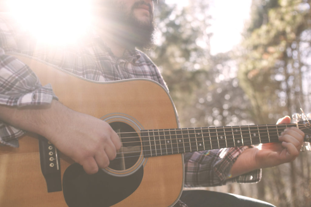 A folk country musician playing his guitar.